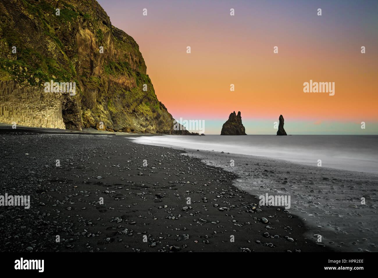 La plage de sable noir de Reynisfjara qui jouit et le mont Reynisfjall près du village de Vik dans le sud de Photo Stock