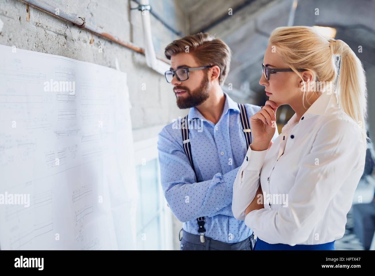 Deux designers brainstorming pensée nouveau projet au bureau moderne Banque D'Images