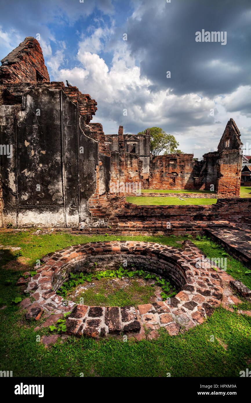 Les murs en ruine antique et bien de Temple à Lopburi, Thaïlande ciel au coucher du soleil Photo Stock