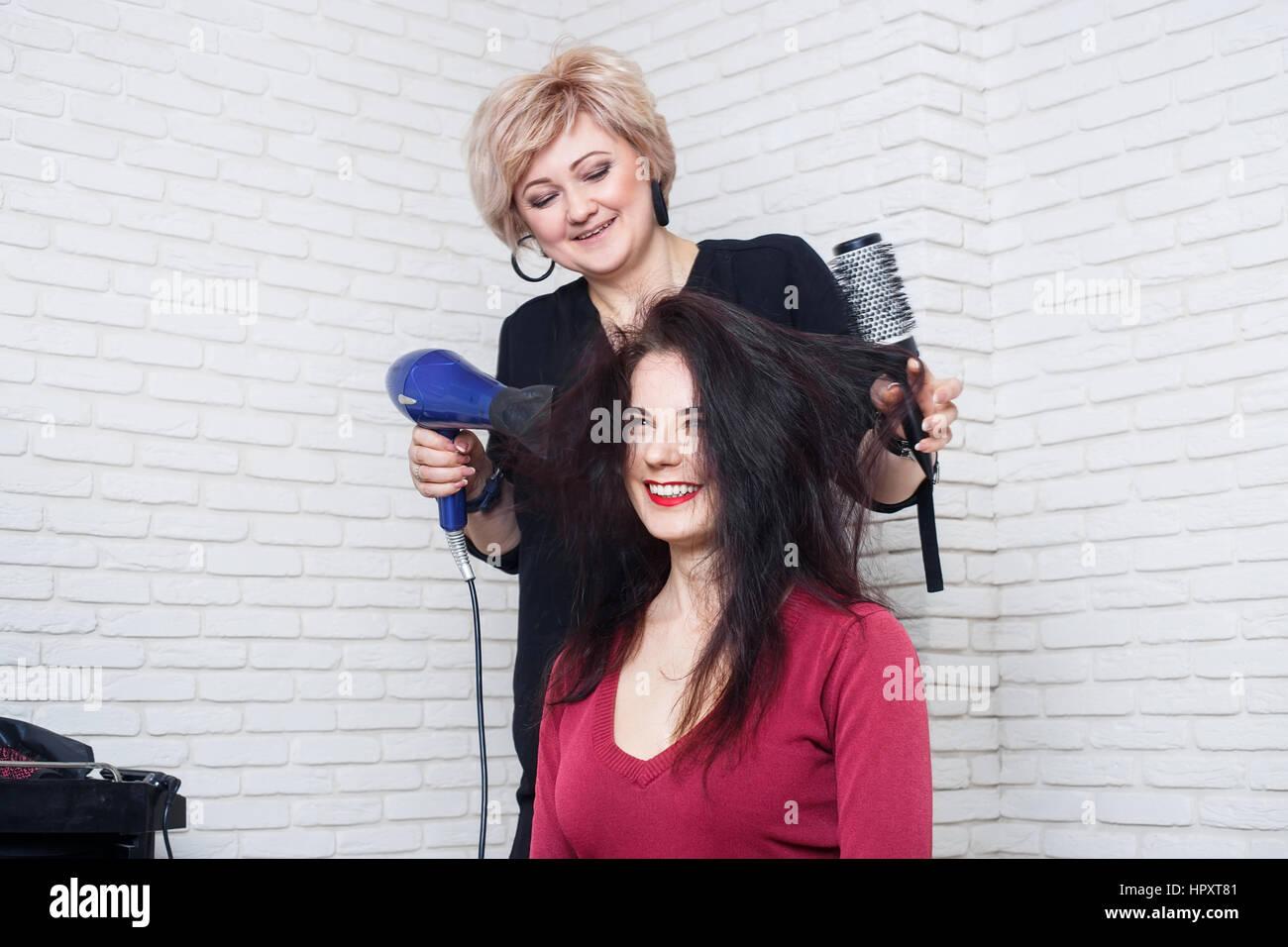 Belle femme à la coiffure blow sécher ses cheveux. Les cheveux de séchage avec un sèche-cheveux Photo Stock