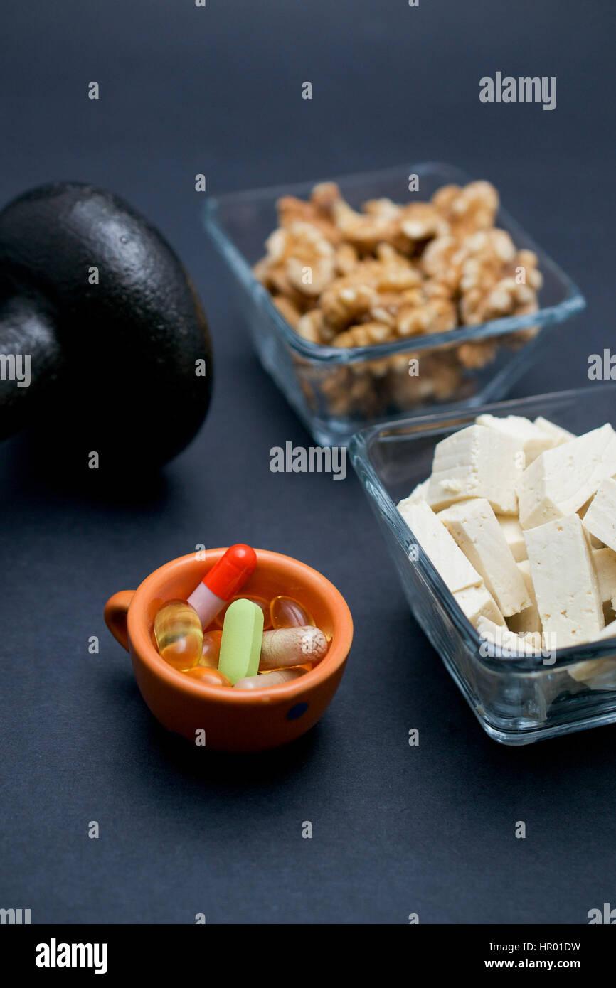 Haltère, tofu, noix et de suppléments alimentaires sur fond sombre: concept de perte de forme physique Photo Stock