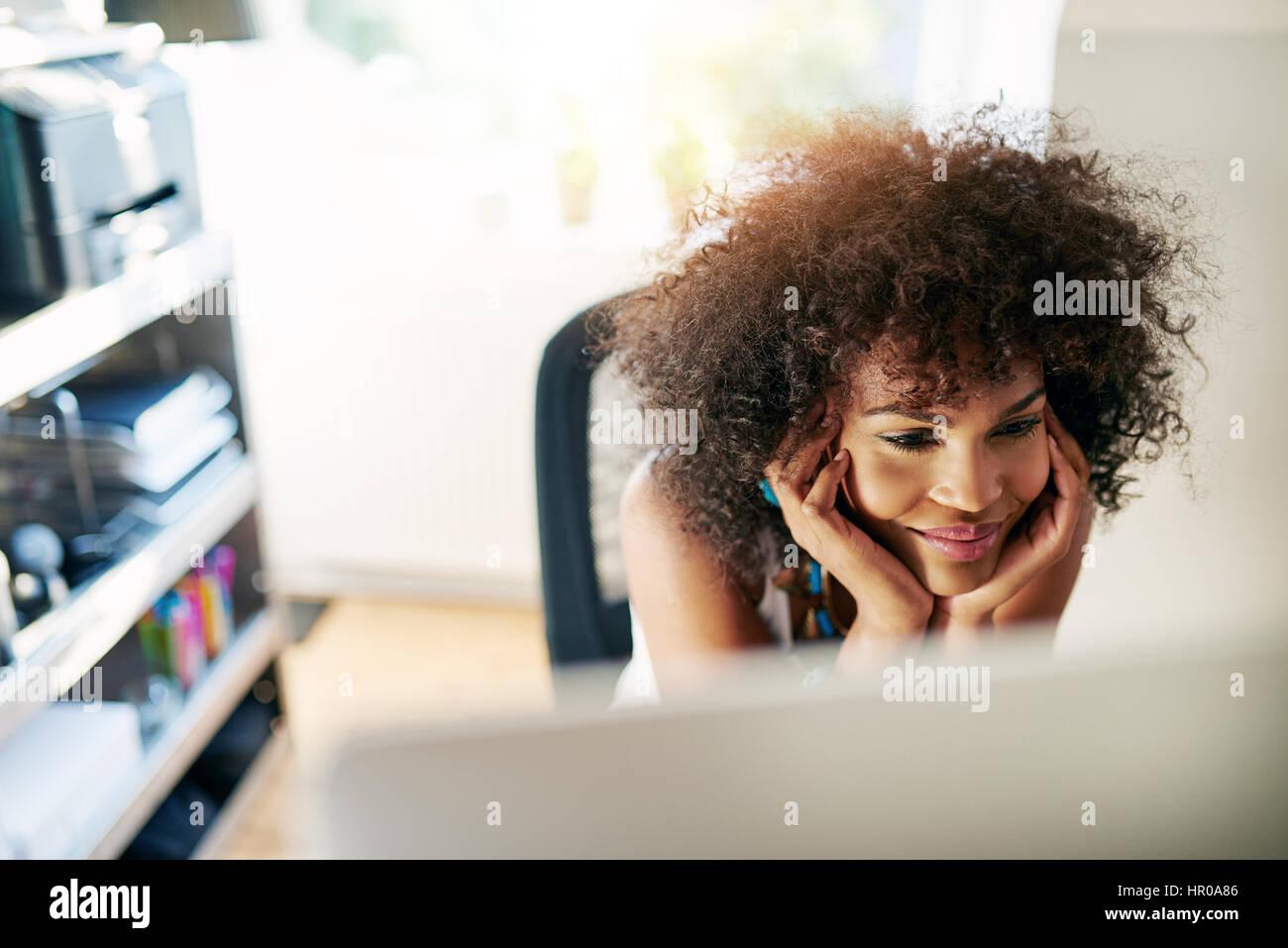 Jolie jeune femme afro-américaine à la recherche de bureau et sourit à l'arrière-plan flou Photo Stock