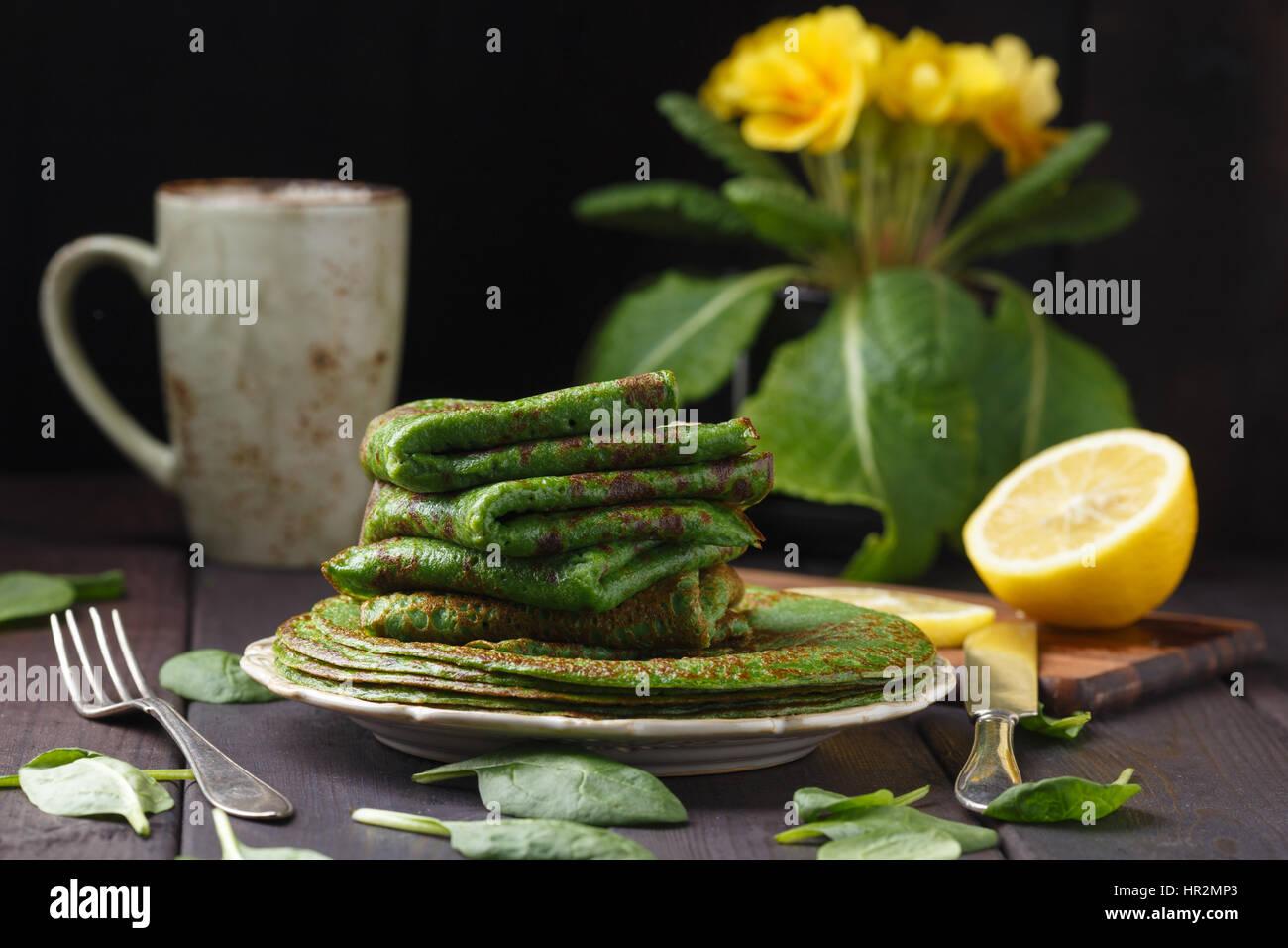 Crêpes aux épinards sur table en bois et jaune primevère. Photo Stock