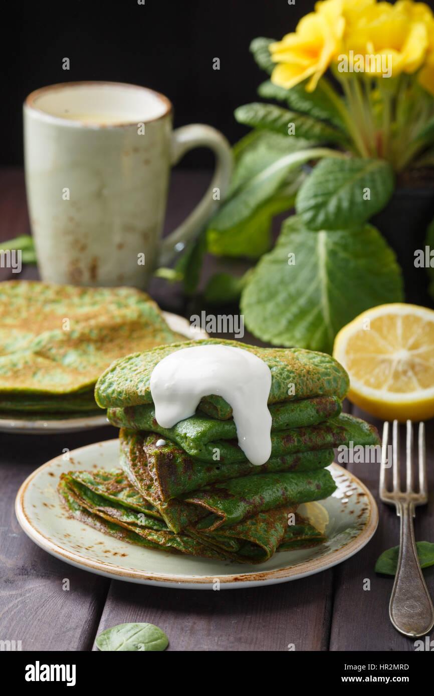 Crêpes aux épinards et à la crème sur la table en bois. Photo Stock