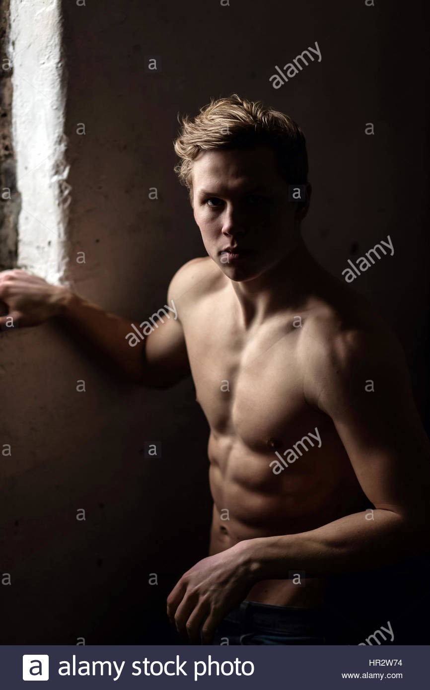Jeune homme torse nu près d'une fenêtre Banque D'Images