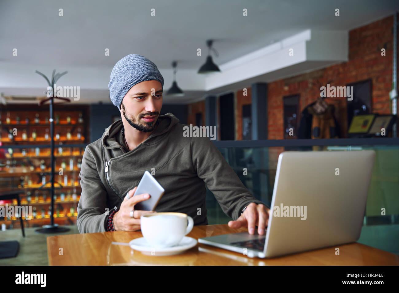Beau jeune homme hipster avec barbe est à l'aide d'ordinateur dans une cafétéria Photo Stock