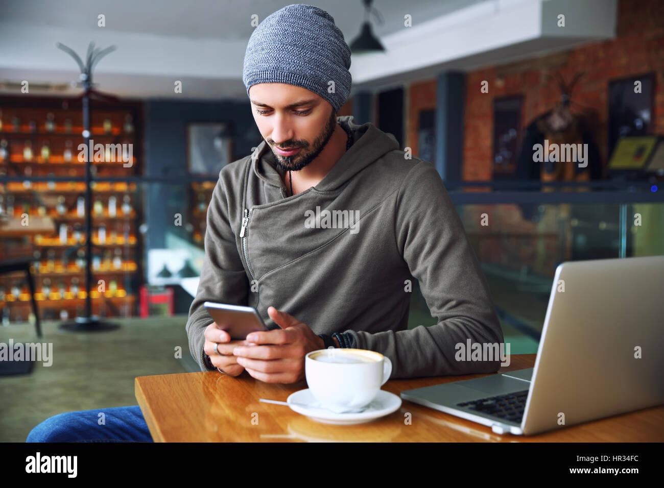 Beau jeune homme hipster au restaurant à l'aide d'un téléphone mobile. Photo Stock