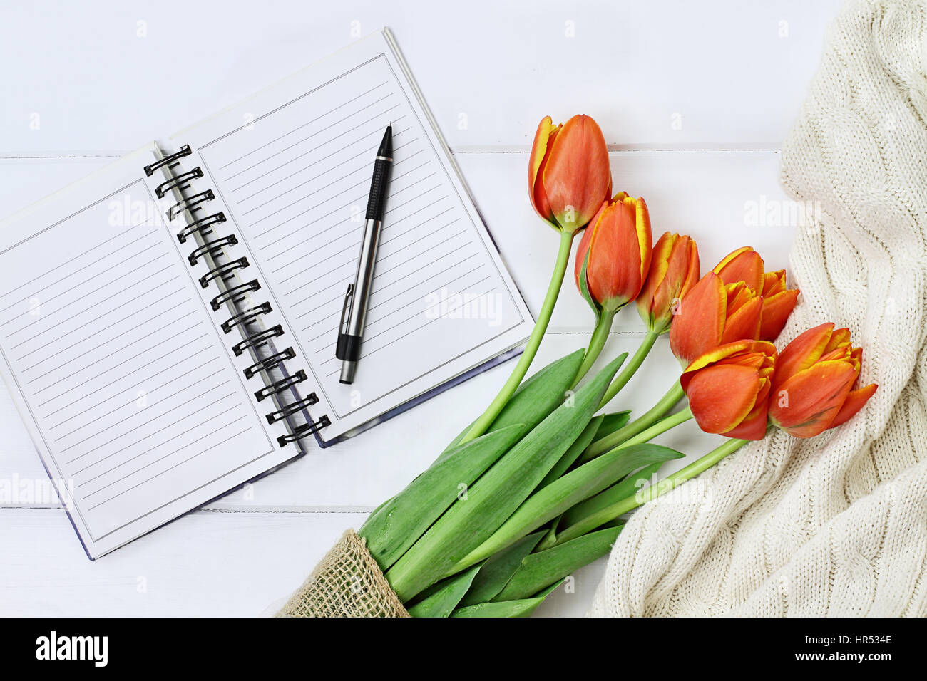 Passage tourné un bouquet de tulipes orange et jaune et un jet de tricot couverture sur bois blanc table top avec Banque D'Images