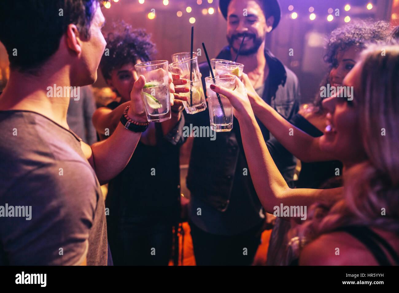 Groupe de jeunes amis au club with cocktails. Les jeunes hommes et femmes à discothèque fête avec Photo Stock