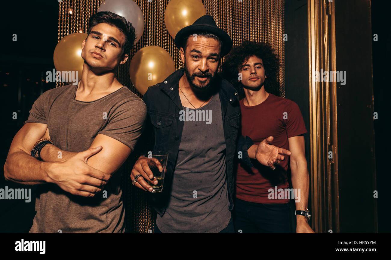 Portrait de trois jeunes hommes debout dans une discothèque. Groupe d'hommes élégants au pub. Photo Stock