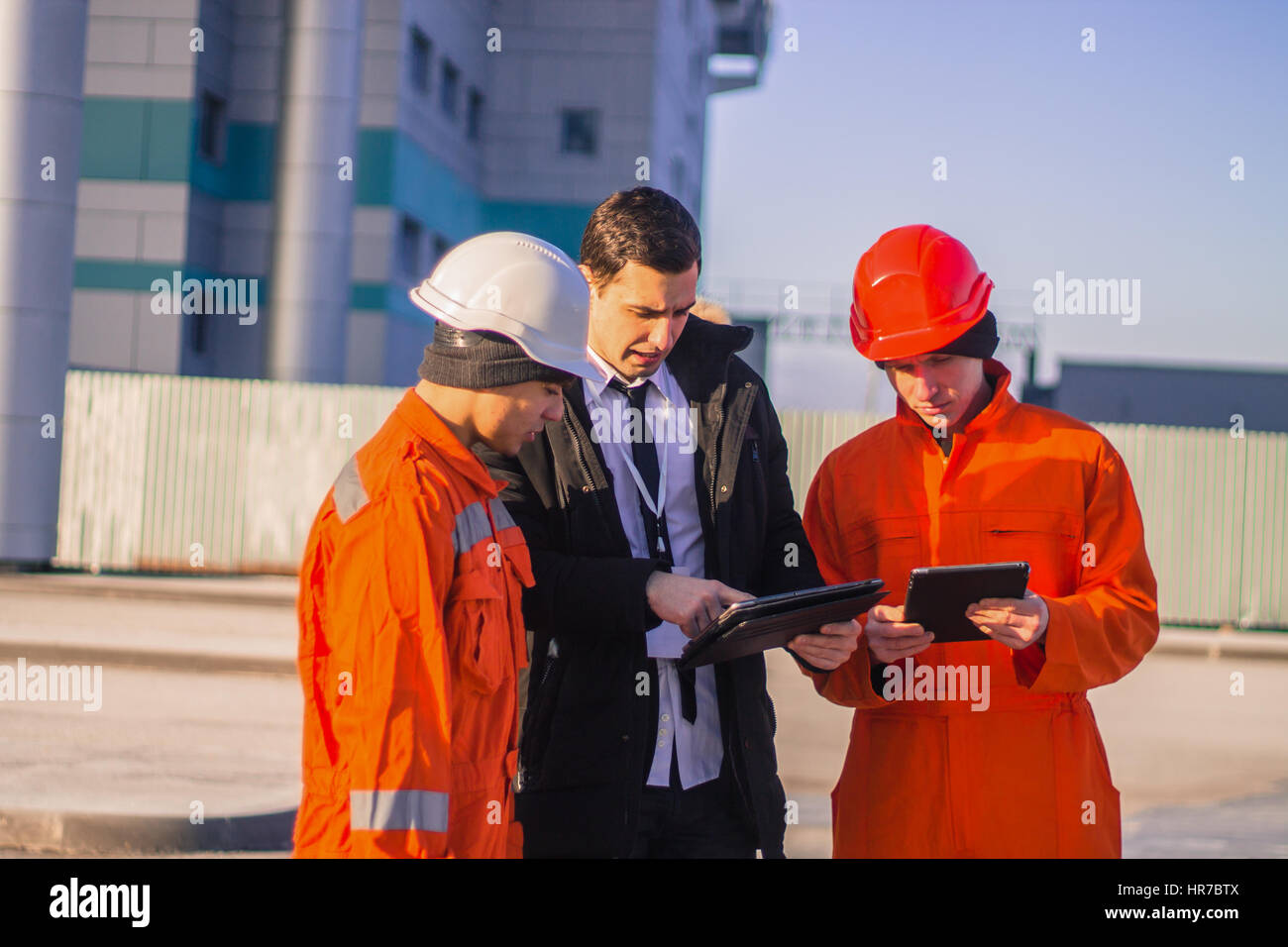 Patron ou chef d'équipe de jeunes demande à de jeunes ingénieurs avec un projet de construction. Photo Stock