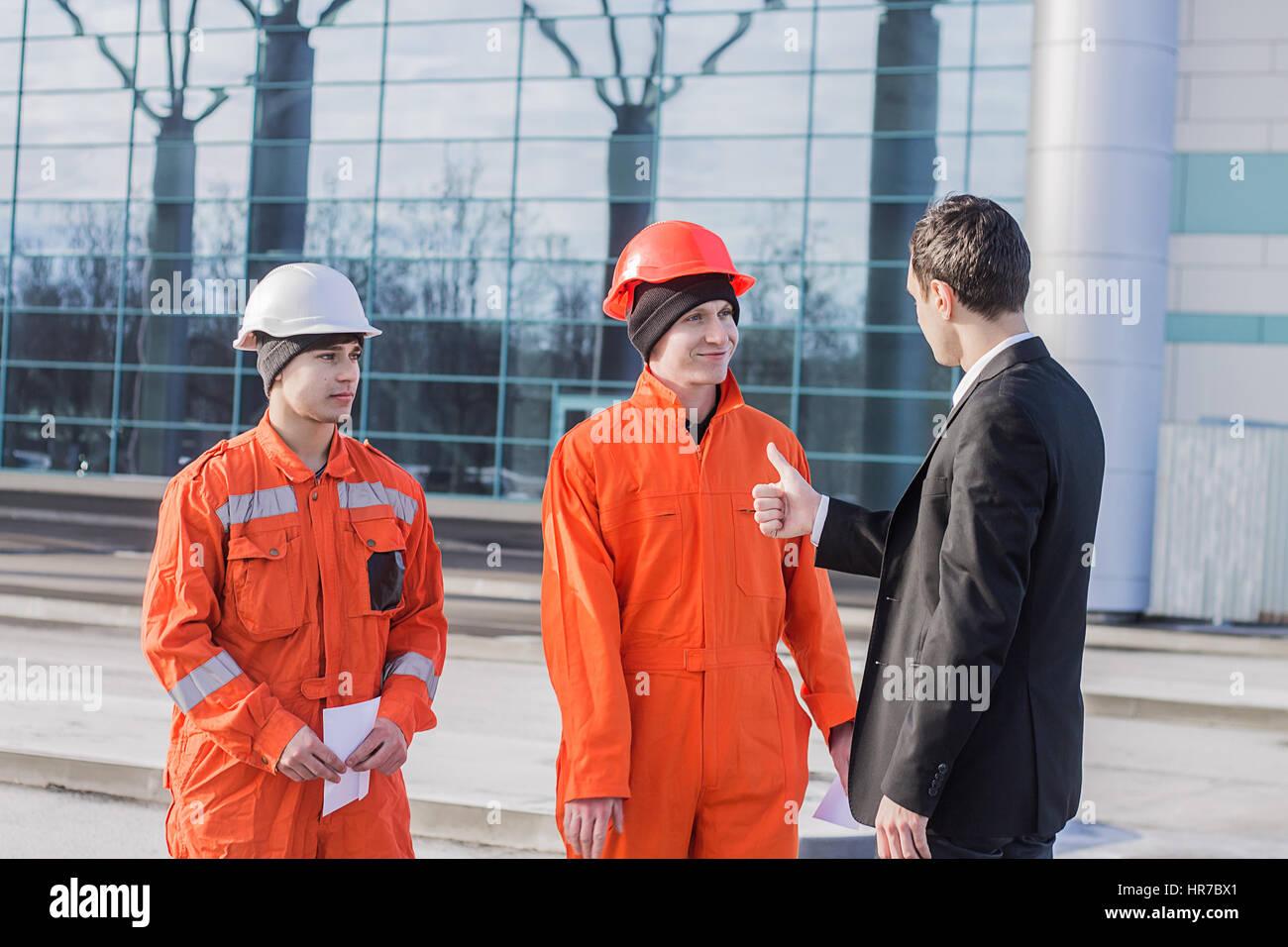 Patron ou chef showing Thumbs up à l'équipe de jeunes ingénieurs. Moderne d'affaires historique. Photo Stock