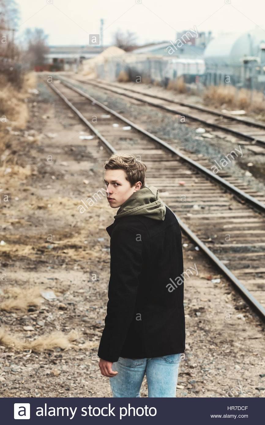 Jeune homme marche loin près des voies de chemin de fer Banque D'Images