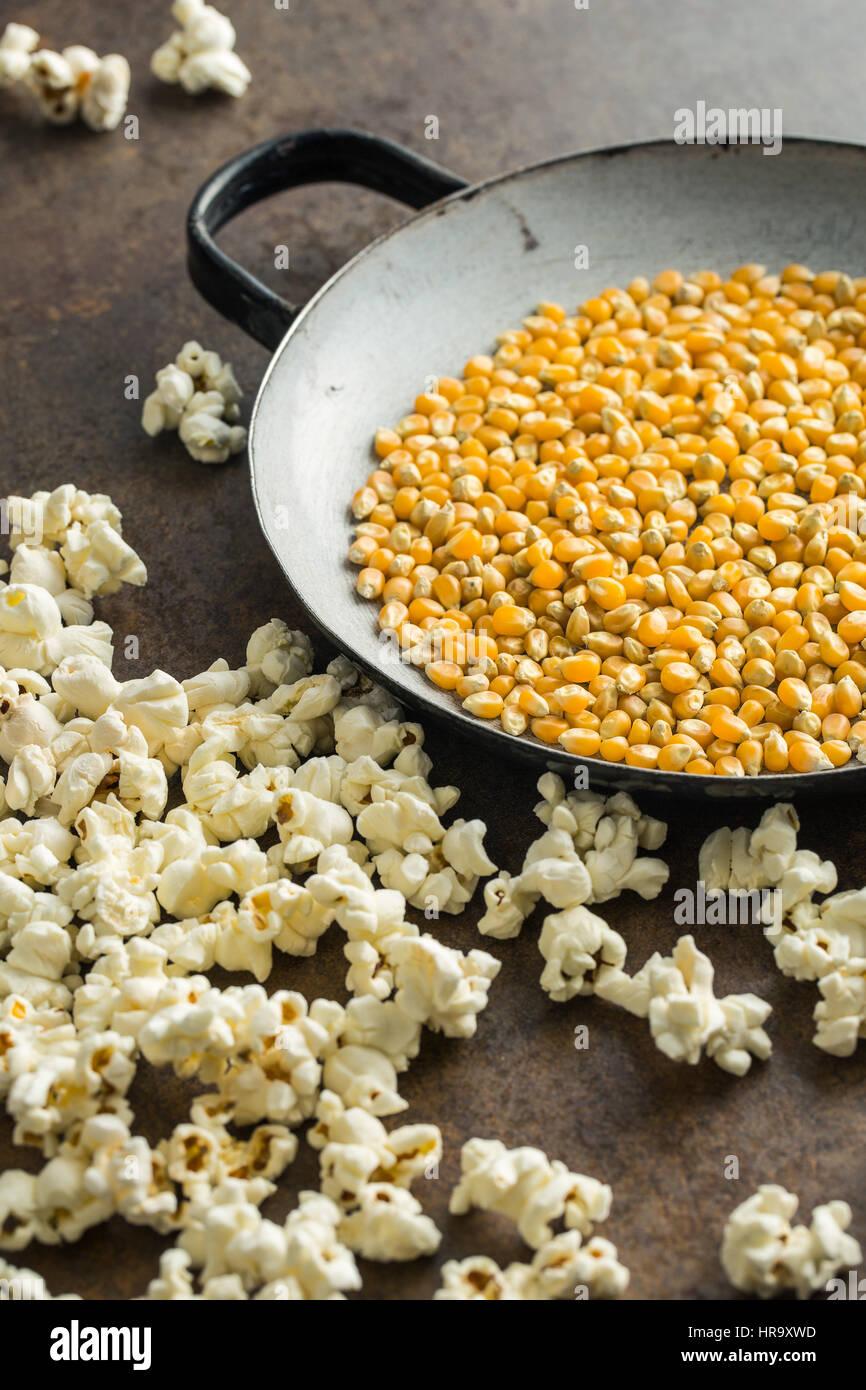 Pop-corn et de semences de maïs sur fond rouille. Photo Stock