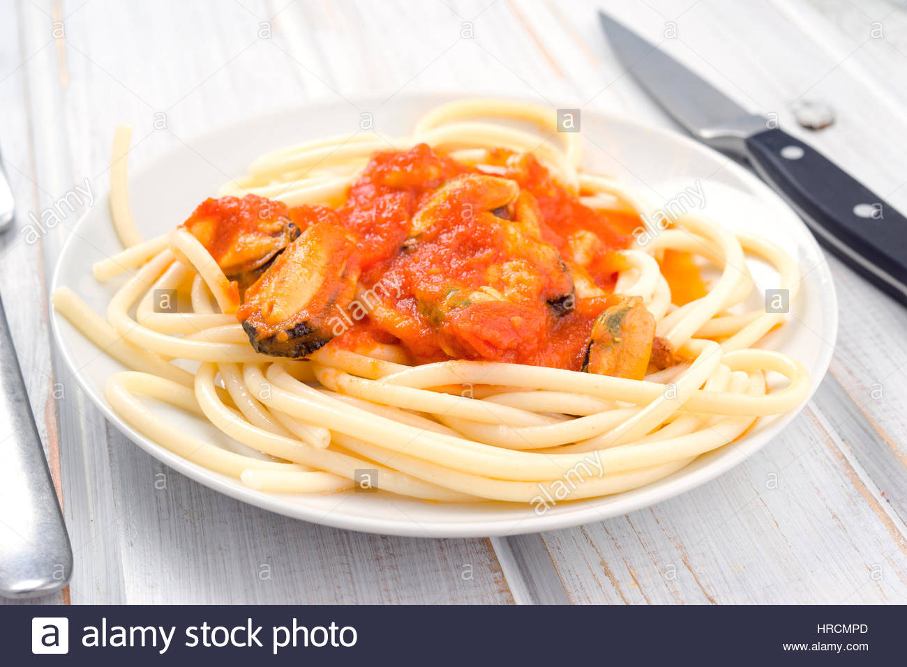 Spaghetti aux crevettes et moules à la sauce tomate dans un plat blanc de Chine Photo Stock
