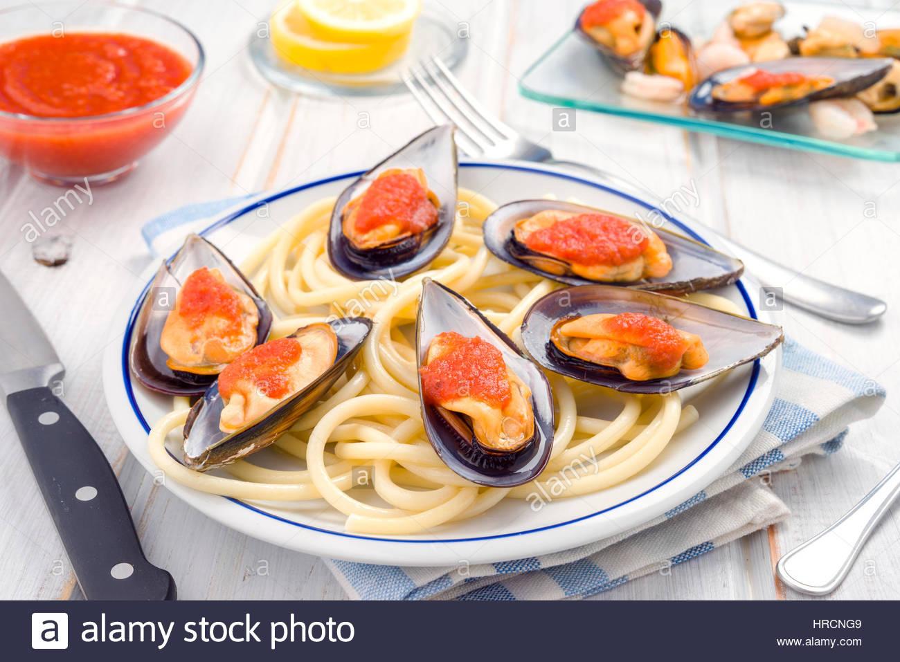 Spaghettis et moules à la sauce tomate dans la porcelaine blanche lave Photo Stock