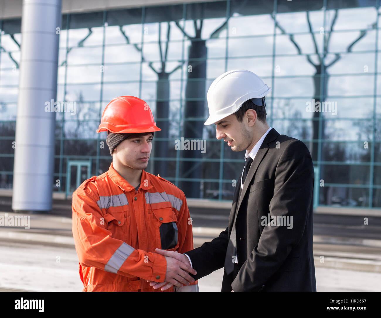 Patron ou chef de l'établissement de liaison avec l'ingénieur du travailleur. Bon travail. Contexte Photo Stock