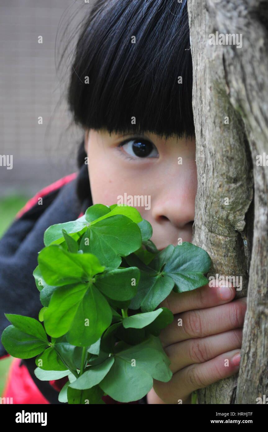 Jeune fille timide derrière un arbre joue à cache-cache Photo Stock