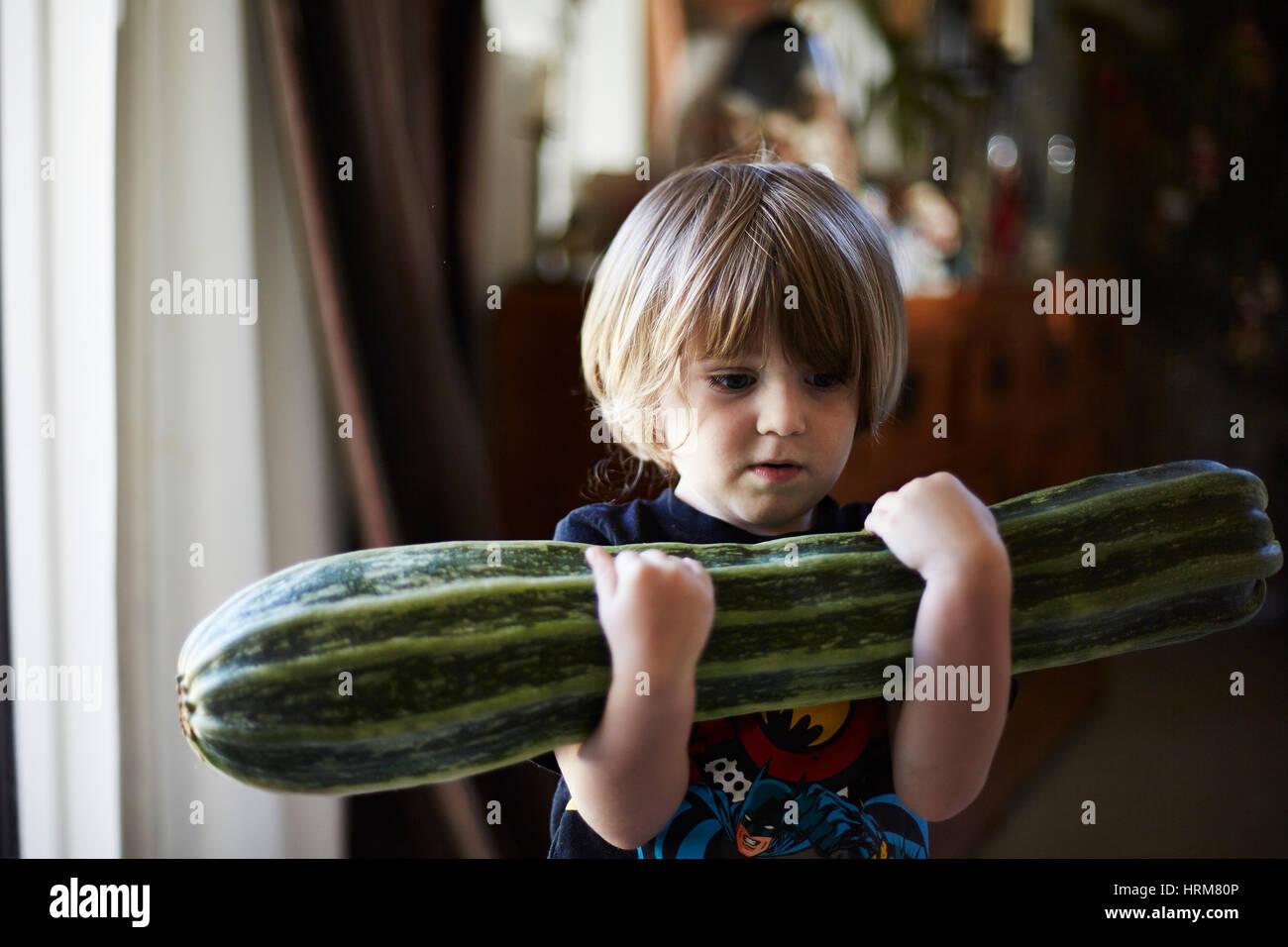 Jeune garçon avec de grandes courgettes Photo Stock