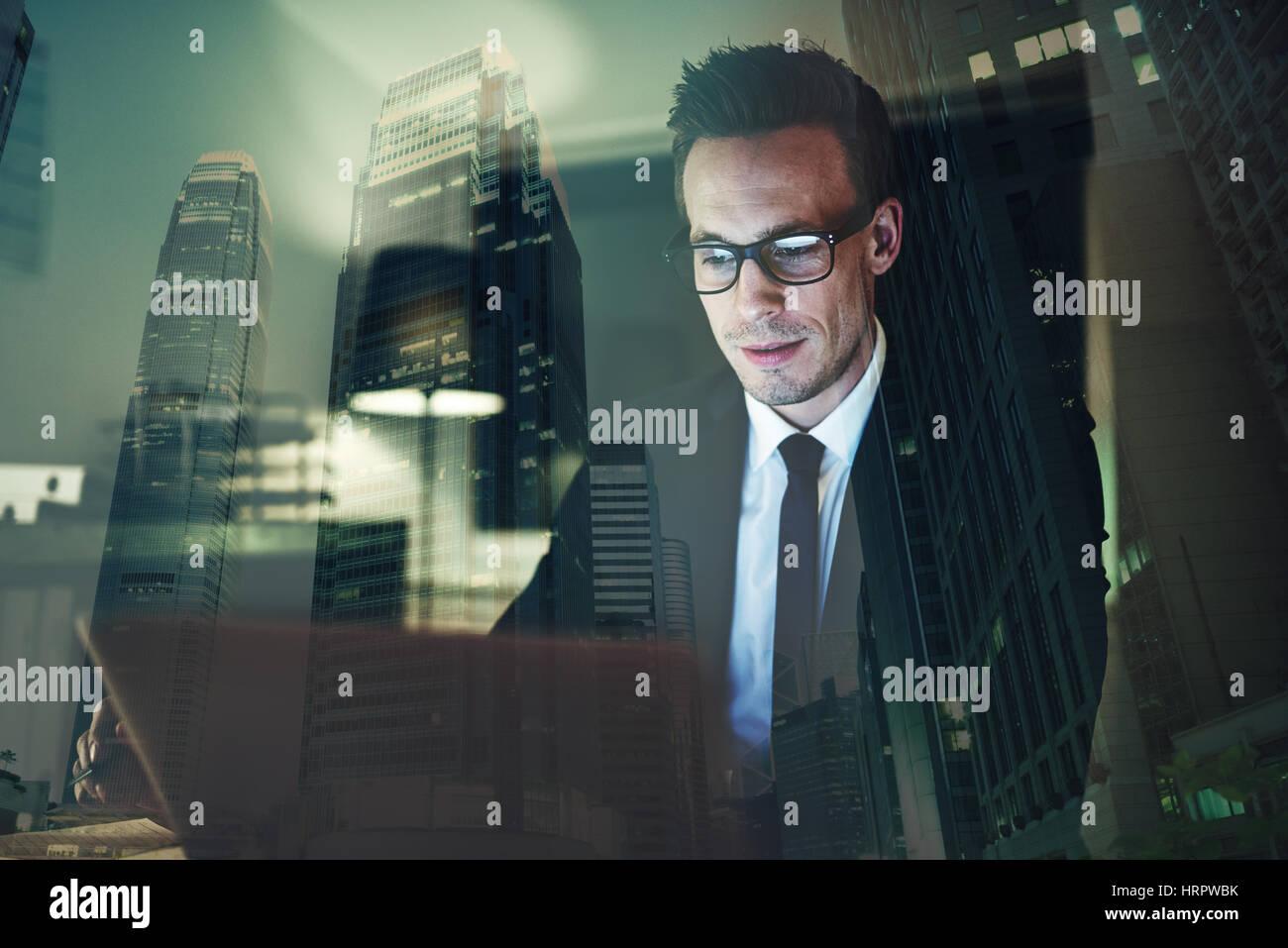 Optimiste businessman working on laptop at office dans la nuit, des heures supplémentaires avec grande ville Photo Stock