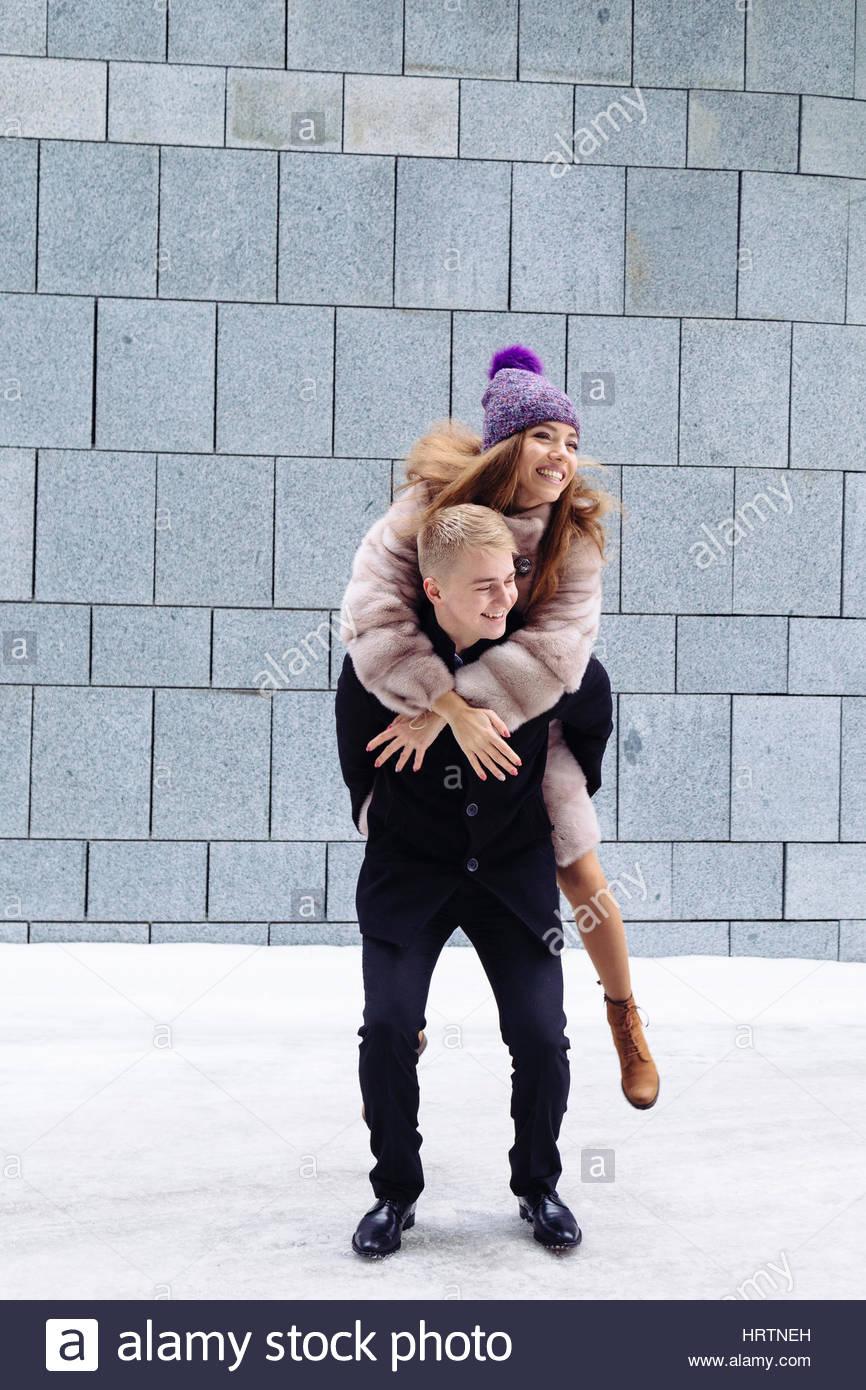 Portrait of a handsome man piggybacking son amie en vacances. relation concept. Photo Stock