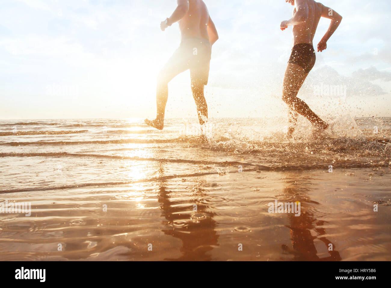 Les amis de s'amuser dans la mer au coucher du soleil plage, enfance heureuse Photo Stock