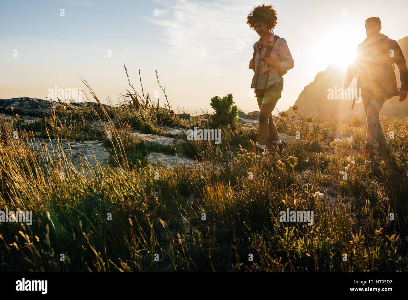Amis de marcher dans la campagne ensemble. Jeune homme et femme en randonnée sur une journée d'été. Banque D'Images