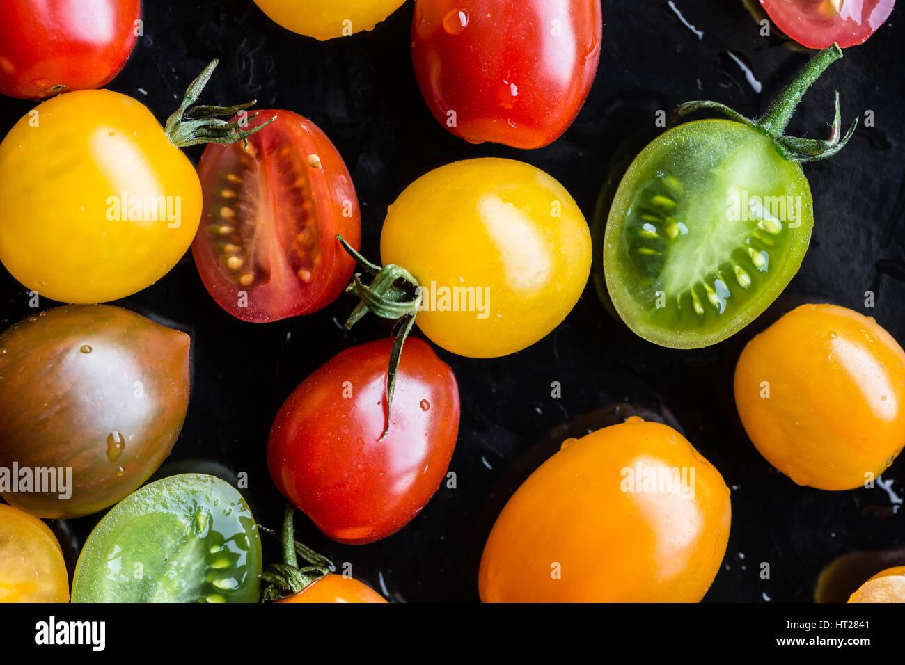 Tomates multicolores sur fond noir Photo Stock