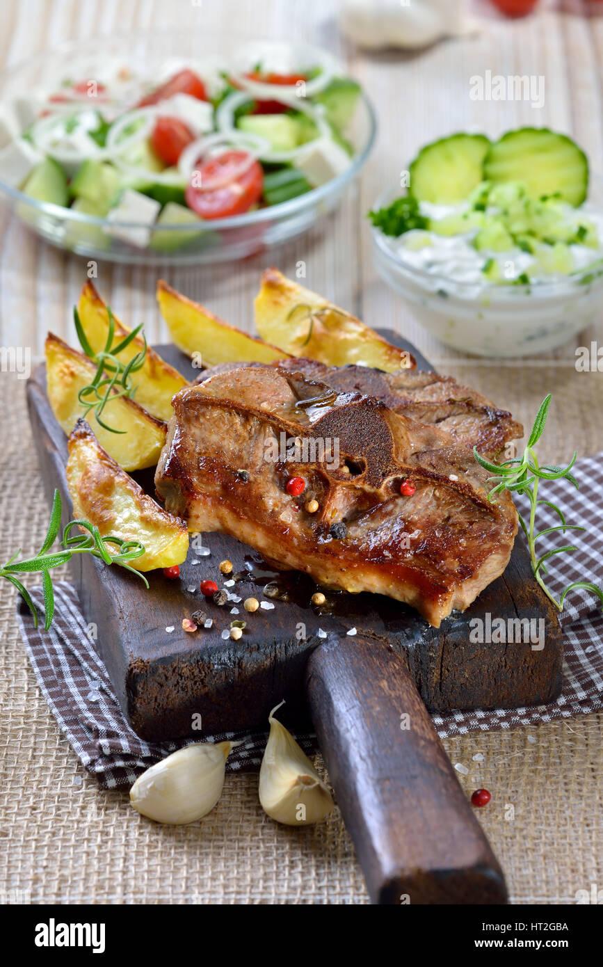 Repas grec: Poêlée de côtelettes d'agneau au four avec les quartiers de pommes de terre, Photo Stock