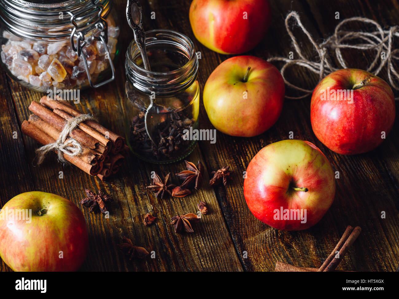 Pommes rouges avec différentes épices sur table en bois. Banque D'Images