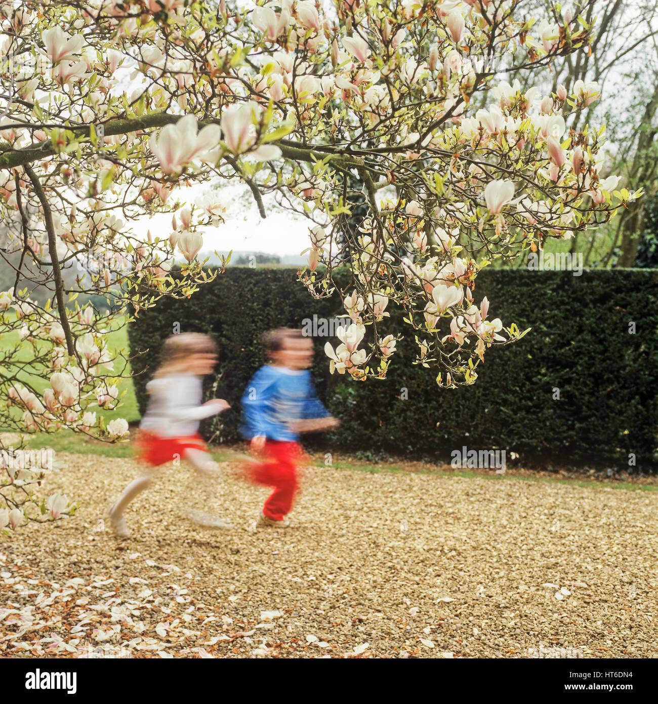 Les enfants courir dans un jardin. Photo Stock