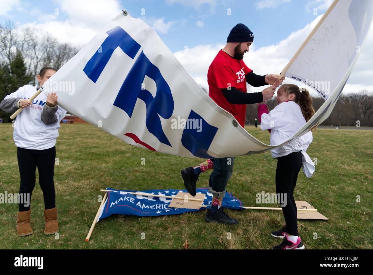 Kaylee et Eva comme Pigiannantonio aide Pete, au nord-est de Philadelphie, lutte avec le vent comme ils se déroulent un grand TRUMP 2016 banner, en prévision d'un pro Banque D'Images