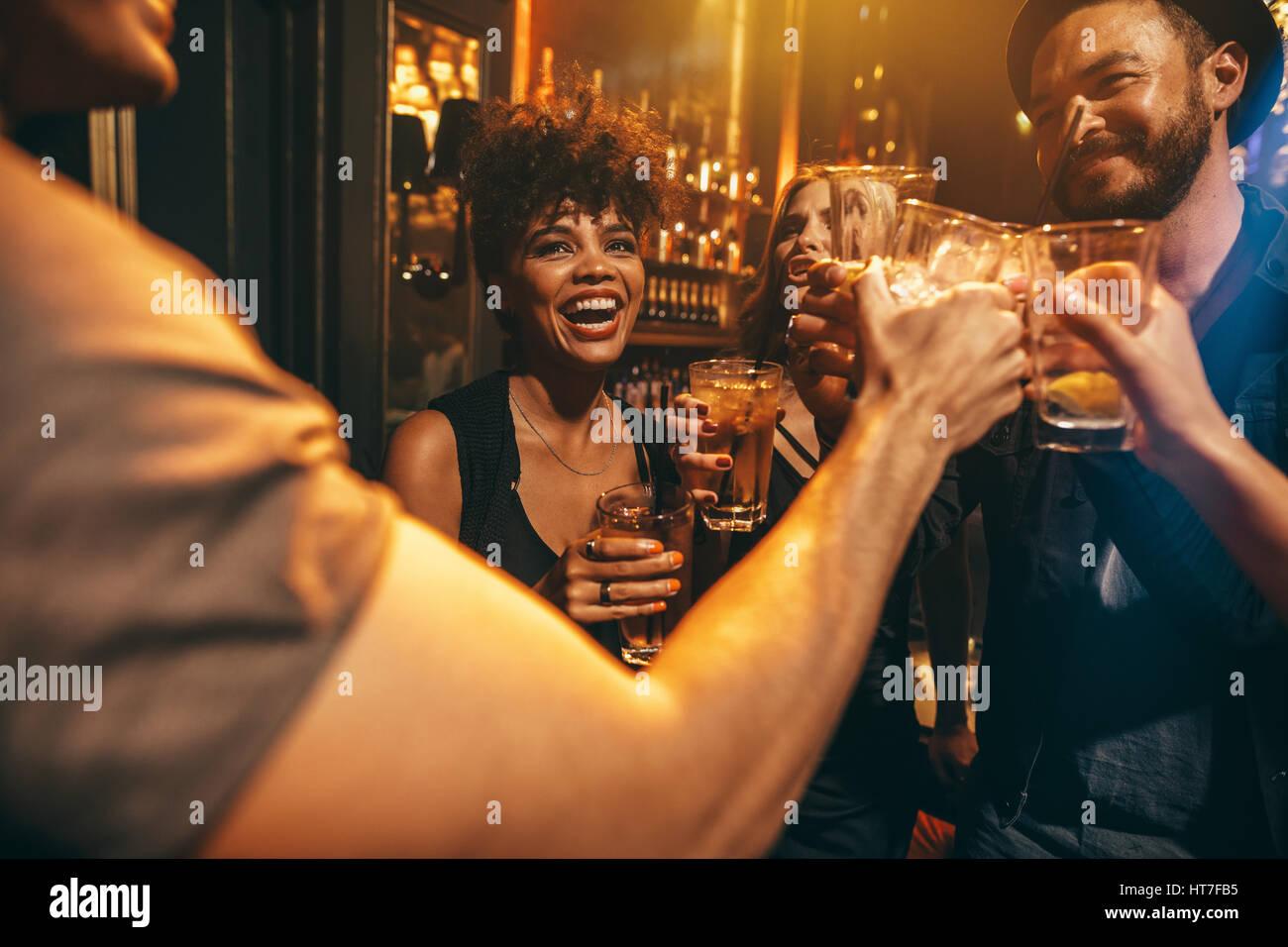Groupe de jeunes toasting drinks at nightclub. Les jeunes hommes et femmes s'amuser au bar-salon. Photo Stock
