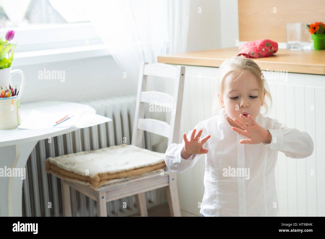 Petite fille essayant de sécher ses ongles fraîchement peint Photo Stock