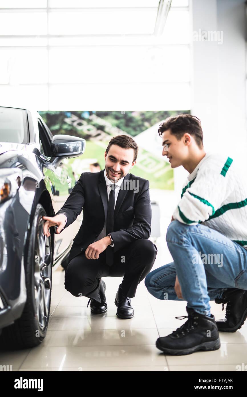 Regardez ces pneus. Jeune vendeur de voiture montrant les avantages de la voiture au client Photo Stock