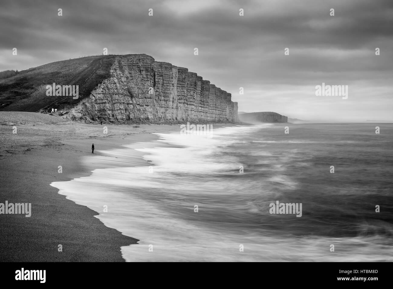 Une figure solitaire regardant des vagues se brisant sur la plage sous falaise Est, West Bay, sur la côte jurassique, Banque D'Images