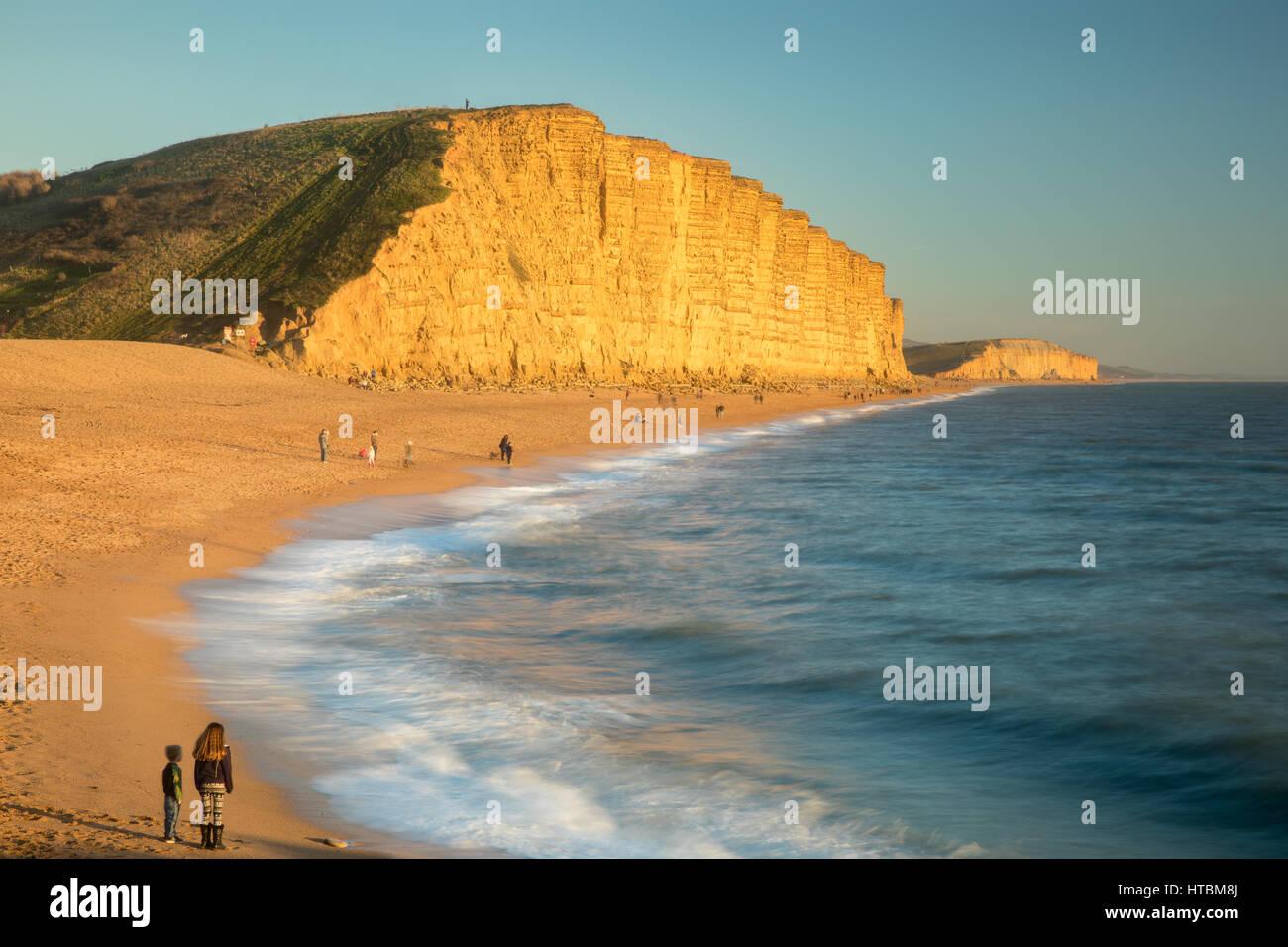 Frère et soeur à regarder les vagues sur la plage ci-dessous East Cliff, West Bay, sur la côte jurassique, Dorset, England, UK Banque D'Images