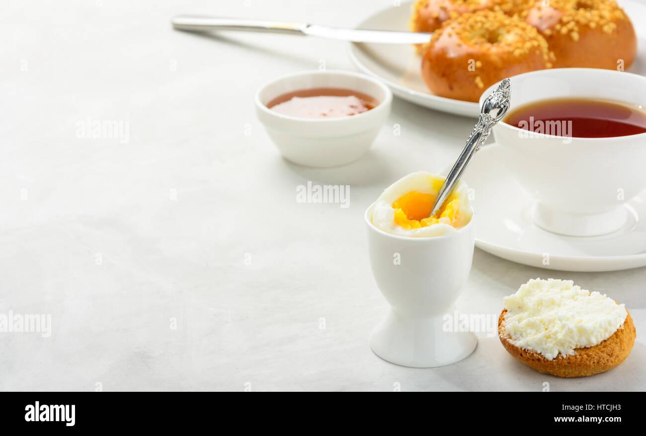 Petit-déjeuner délicieux et sains de l'oeuf mollet et brioches brioche avec du thé noir sur fond Photo Stock
