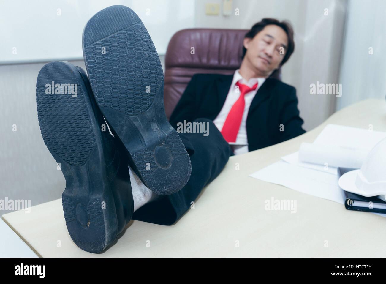 Businessman de mettre les pieds sur le bureau en bureau banque d