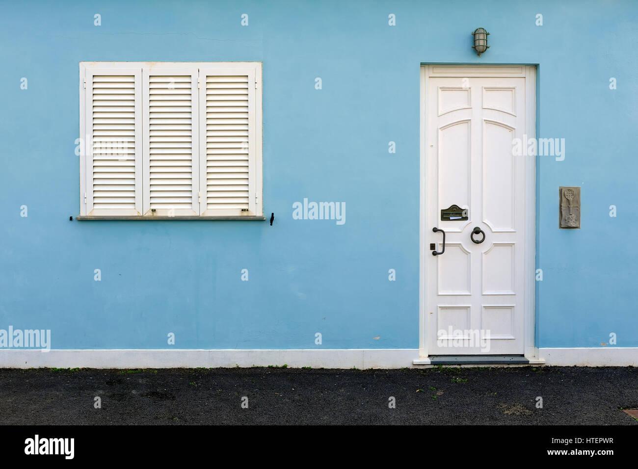 Light blue façade de maison avec porte et fenêtre blanche typique de la Méditerranée - maison Photo Stock