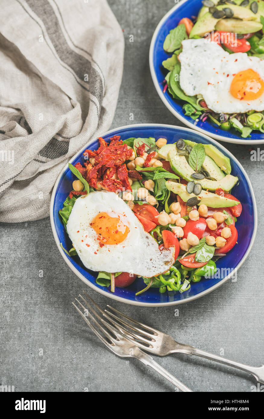 Petit-déjeuner sain avec des oeufs frits, les pois chiches, les légumes, les graines et les verts Photo Stock
