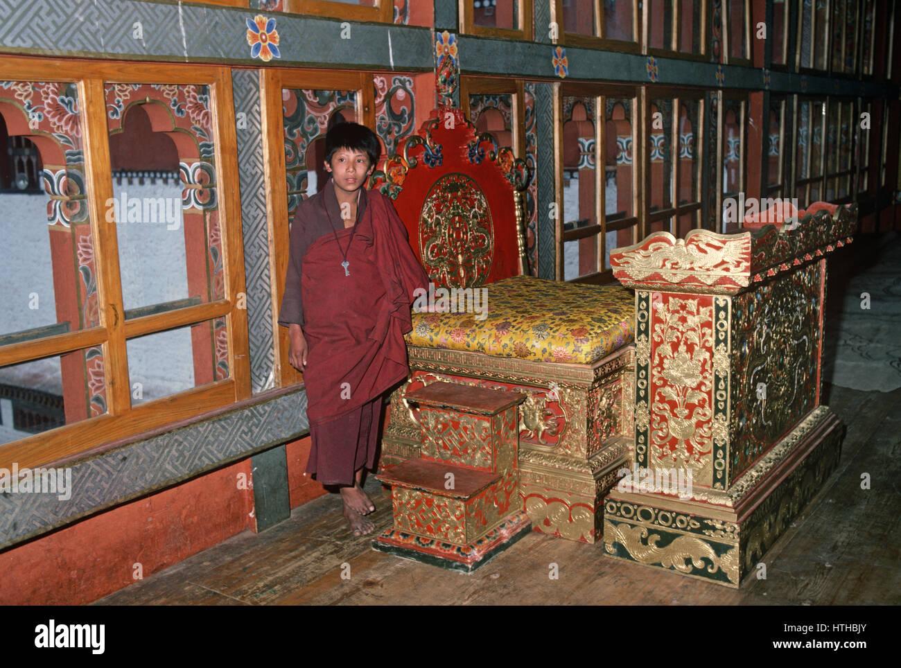 Jeune moine bouddhiste debout à côté de Kings trône, Tashichhodzong, monastère bouddhiste Photo Stock