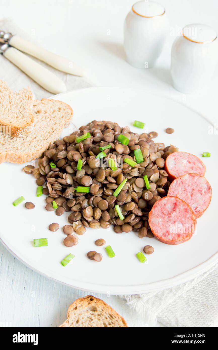 Avec des lentilles vertes (saucisse cotechino) on white plate Photo Stock