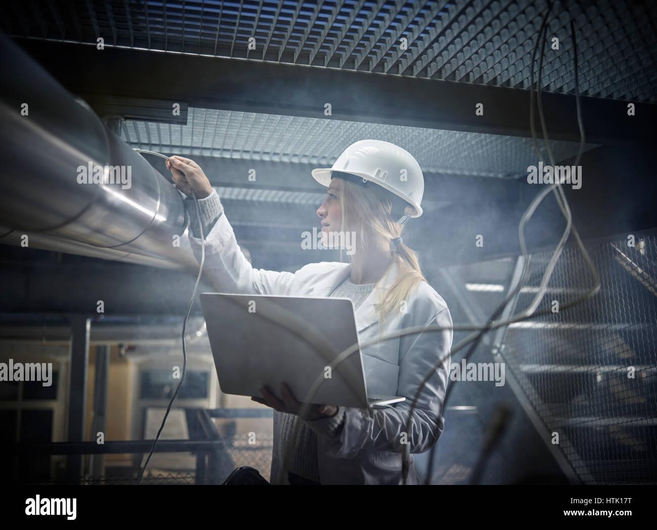 Jeune femme avec casque, sarrau blanc et l'ordinateur portable debout devant une usine industrielle, Autriche Banque D'Images
