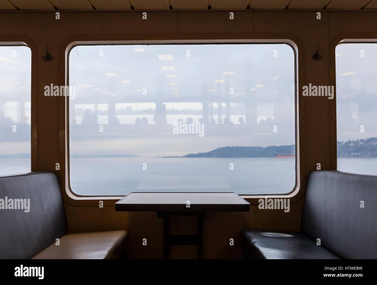 D'un coin salon dans un Washington State Ferry avec une table et fenêtre donnant sur un jour nuageux. Photo Stock