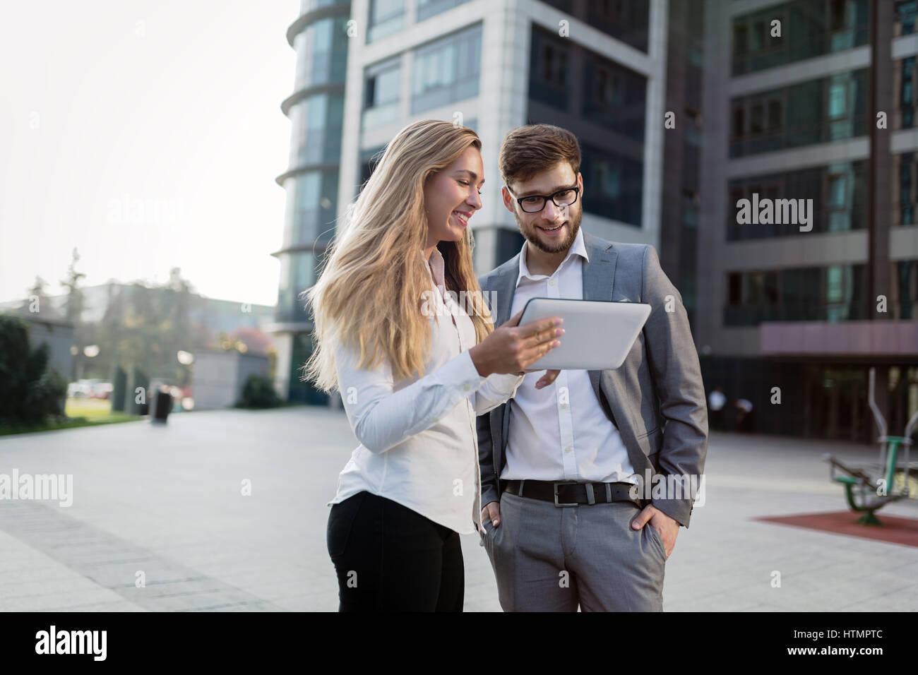 Les gens d'affaires la marche à l'extérieur et à l'aide de téléphones mobiles tablettes Banque D'Images