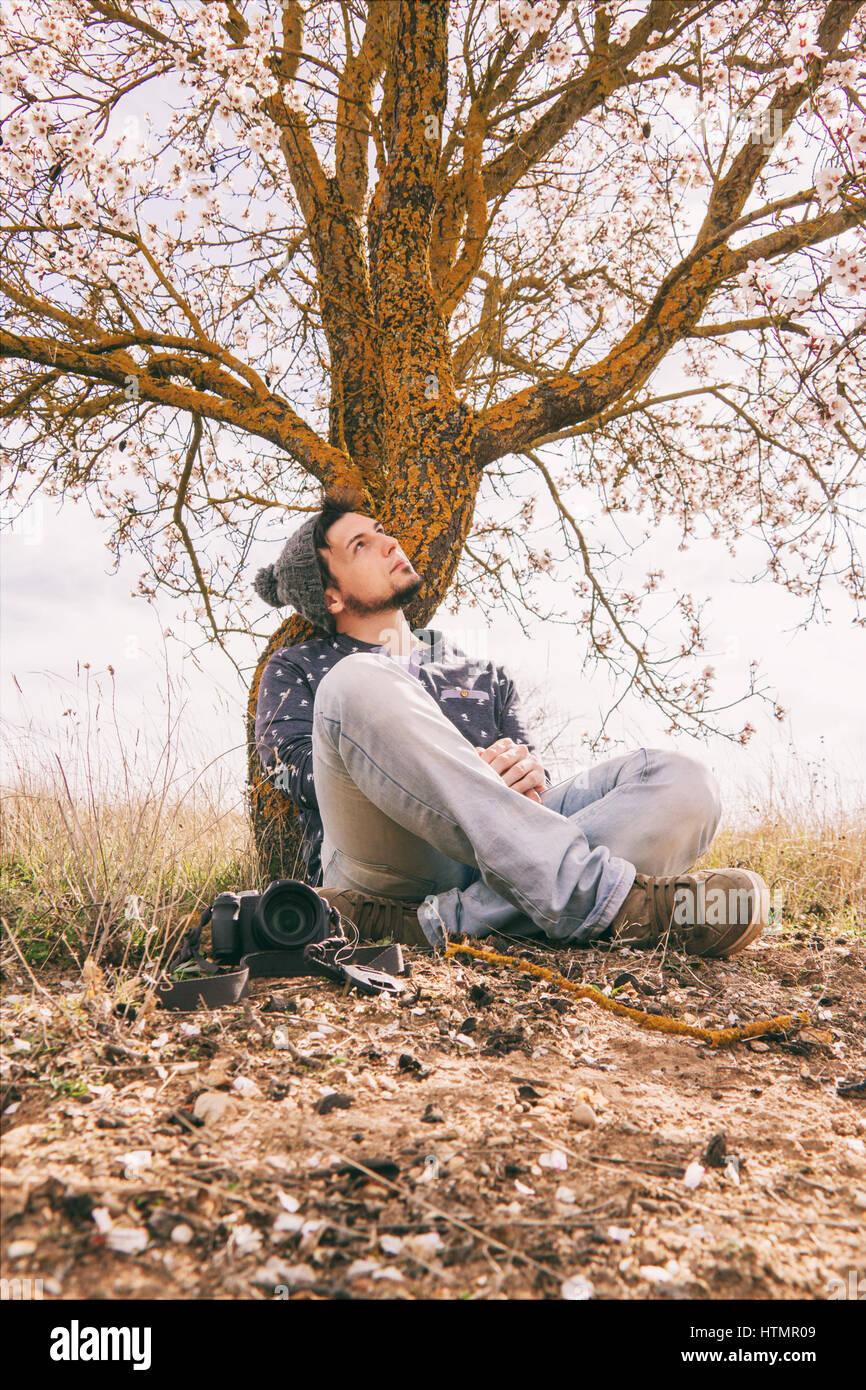 Jeune homme hipster de prendre des coups de près d'un arbre en fleurs au printemps Photo Stock