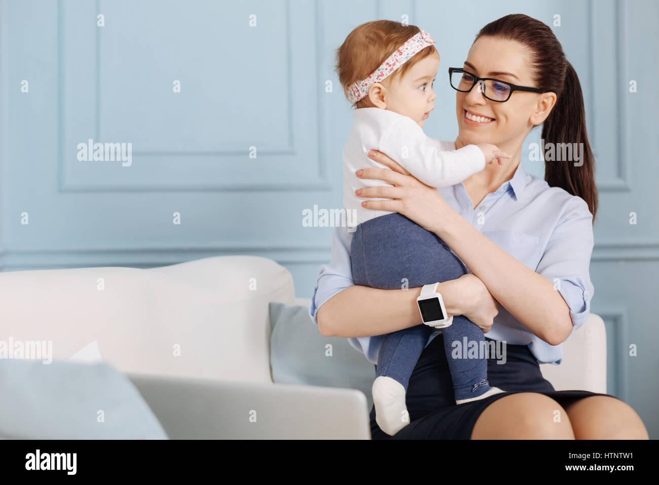 Doux et attentionné. Jeune femme énergique accompli assis sur un canapé et de dépenser sa pause avec sa petite fille tout en travaillant de chez vous. Banque D'Images