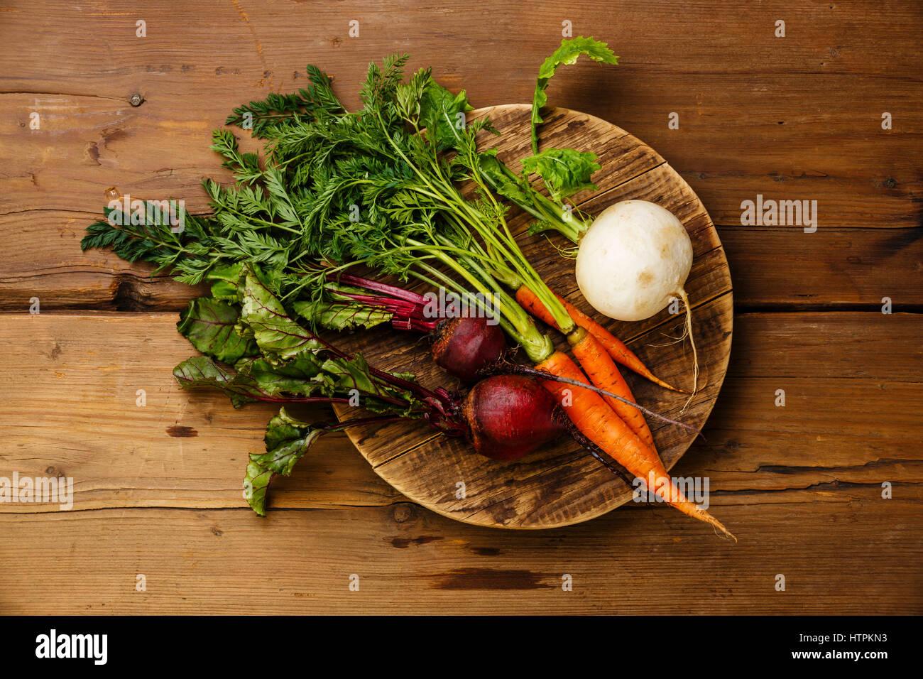 Légumes frais, carottes, navets et betteraves sur la planche à découper ronde sur fond de bois Photo Stock