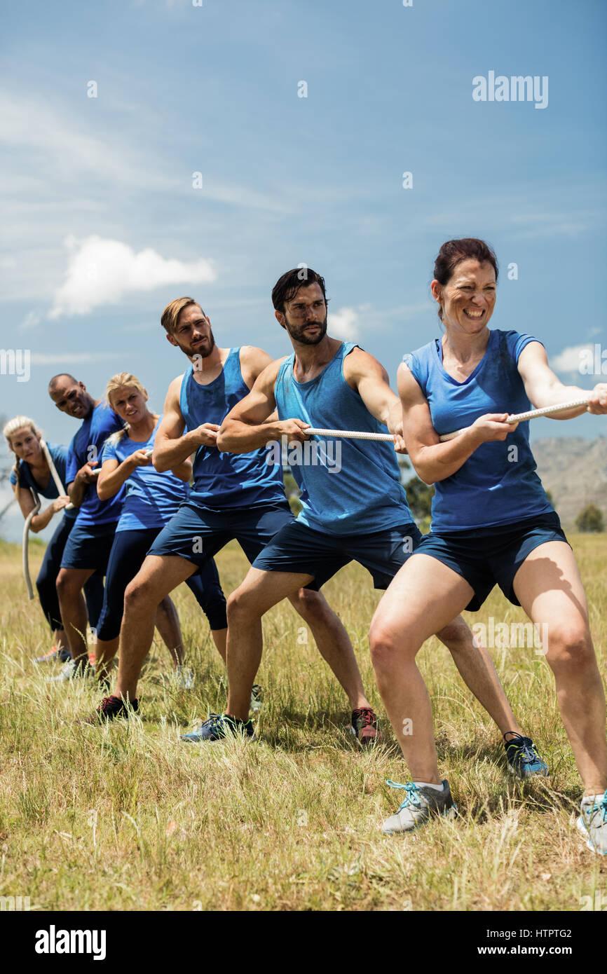 Gens jouer remorqueur de la guerre au cours d'obstacle dans boot camp Cours de formation Photo Stock